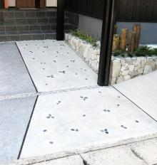 カーブースと兼用のアプローチはコンクリートの仕上げを変えて那智黒を散らしました